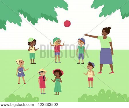 Children Play Ball In Nature Under The Supervision Of A Teacher. Boys And Girls Have Fun In The Park