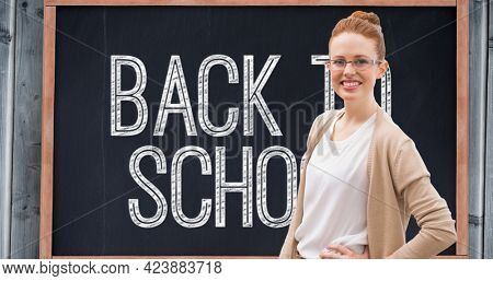Composition of smiling female school teacher over white text back to school on chalkboard. school, education and study concept digitally generated image.