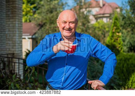 Senior Man At Morning. Holding A Cup Of Tea In Hands. Man Wearing A Blue Shirt Posing At The Camera