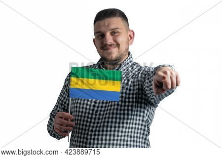 White Guy Holding A Flag Of Gabon And Points Forward In Front Of Him Isolated On A White Background.