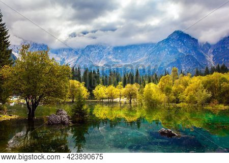The Dolomites are covered with clouds. Lake Fuzine in Northern Italy. Magnificent colors of autumn. Orange and yellow trees are reflected in the green smooth water.