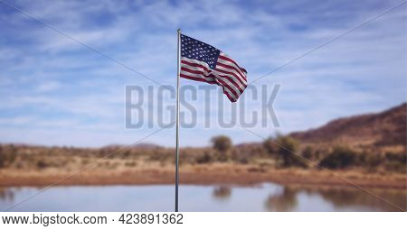 Composition of american flag on flagpole billowing over lake, landscape and blue cloudy sky. patriotism, independence and celebration concept digitally generated image.