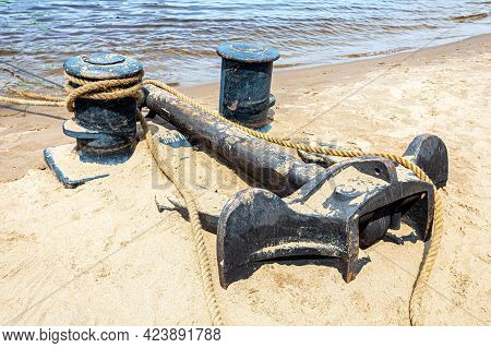 Mooring Bollard With A Fixed Rope And Ship Anchor In The Harbor On The Sand Beach