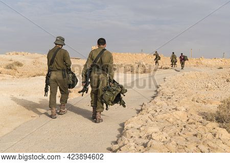 Two Israeli Soldiers On The Foreground Walking On Territory Of Masada Fortification After Prolonged