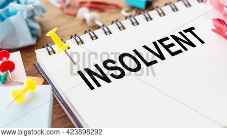 Insolvent - Text On A Notepad With Wrinkled Paper And Paper Needles On Wooden Background.