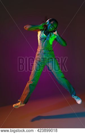 Latino Young Womans Portrait On Dark Studio Background In Neon. Concept Of Human Emotions, Facial Ex