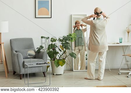 Full Length Back View At Mature Woman Putting On Headscarf While Looking At Mirror And Getting Ready