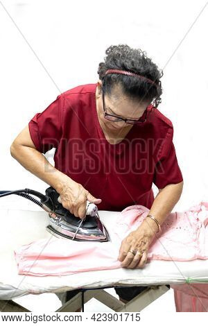 An Elderly Woman Who Is A Housewife Is Ironing Clothes With An Iron, Which Is A Household Chore On I