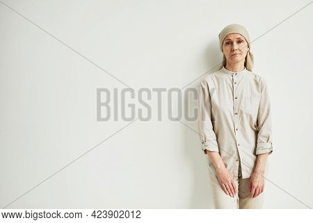Minimal Portrait Of Pensive Mature Woman Wearing Headscarf And Looking At Camera While Standing By W