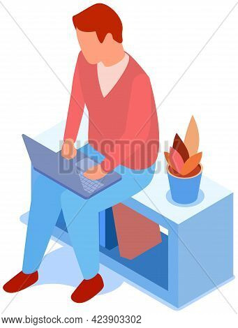 Man In Casual Outfit Sitting On Shelf With Books And Browsing Or Working On Laptop At His Laps. Male