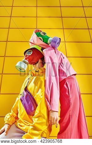 Environmental disaster. Two tender lovers in bright clothes and gas masks stand with their backs to each other by a yellow industrial wall. Love and the apocalypse.