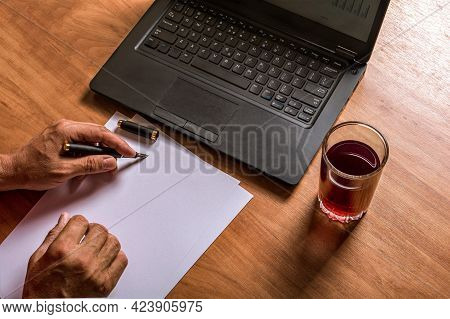 Hands Of A Man Writing With Ink Pen On White Paper. Laptop Keyboard, Glass Of Juice.