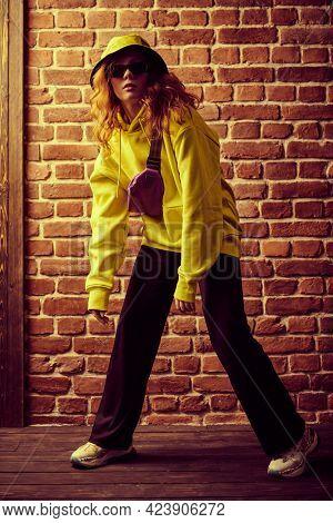 Modern young hip-hop dancer girl in yellow hoodie dancing contemporary urban street dance. Brick wall background.
