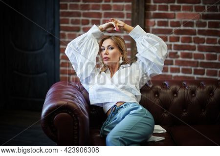 Glamorous middle-aged woman with enlarged full lips and evening makeup lying on a leather sofa. Luxury lifestyle. High fashion shot.