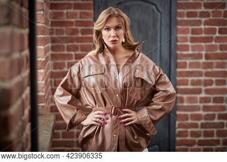 Glamorous middle-aged woman with enlarged full lips poses in a leather coat in loft interior. Luxury lifestyle. Female beauty, fashion.