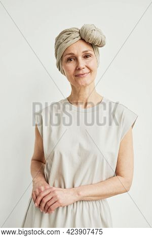 Minimal Vertical Portrait Of Beautiful Mature Woman Wearing Headscarf And Smiling At Camera