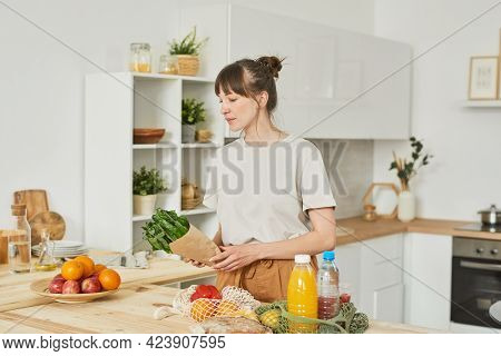 Young Housewife Buying Food For Dinner She Standing In The Kitchen And Putting Food On The Table