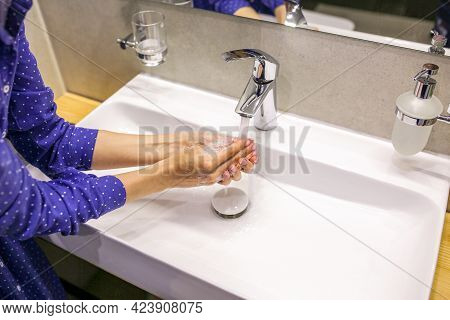 The girl washes her hands in soap. Liquid soap. A drop of soap. Wash your hands during a pandemic. C