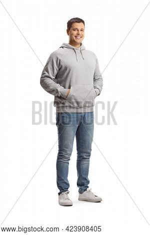 Full length portrait of a young man in a gray hoodie and jeans posing with hands in pockets isolated on white background