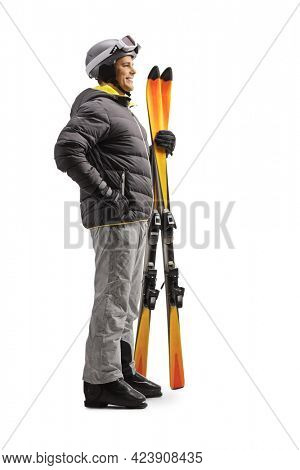 Full length profile shot of a man holding a pair of skis isolated on white background