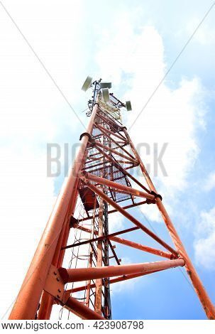 Telecommunication Tower With Antennas On A Background Of Blue Sky And Clouds. Smart Antennas Transmi