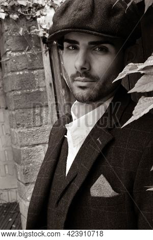Handsome Latino Gangster Dressed In Waistcoat And Jacket Sitting And Looking At Camera, Leaning On G