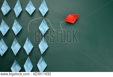 Group Of Blue Paper Boats Are Sailing In One Direction, One Red Is Sailing In The Opposite Direction