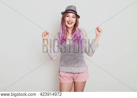Portrait Of Happy Female Wearing Hat, Shirt And Short, Clenching Fist With Satisfied Facial Expressi