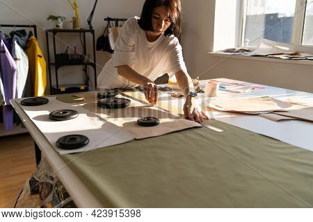 Woman Seamstress Use Chalk And Ruler To Draft Paper Patterns On Textile Material For Clothes Sew. Fe