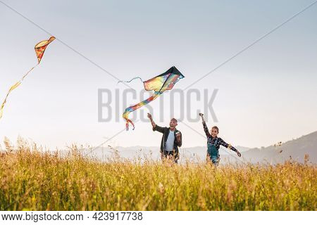Daughter With Smiling Father While They Flying A Colorful Kites On The High Grass Meadow In The Moun