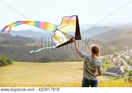 Teenager Boy On The Green Hills Meadow Grass Launching Colorful Rainbow Kite Toy With A Long Tail. H