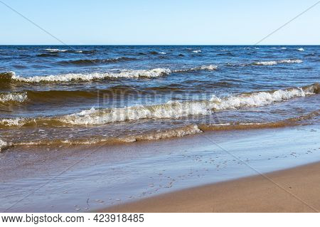 Shoreline At Ragakapa Beach In Jurmala, Latvia. Yellow Sandy Beach And Blue Baltic Sea Waves With Wh