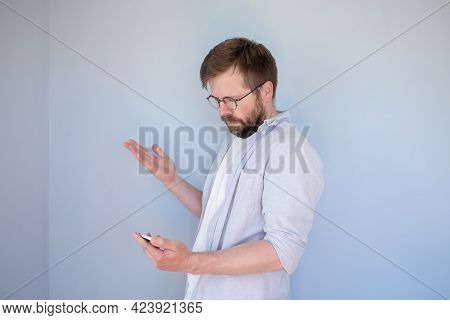 Puzzled Bearded Man In Glasses And Casual Clothes Looks At Smartphone, He Is Confused And Makes A Ha