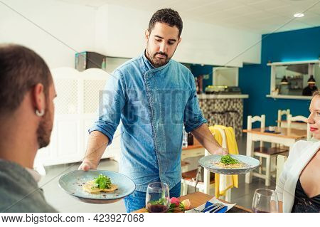Waiter Carrying Two Plates With Pasta Raviolis Dish For Younger Couple In The Restaurant. Food And J