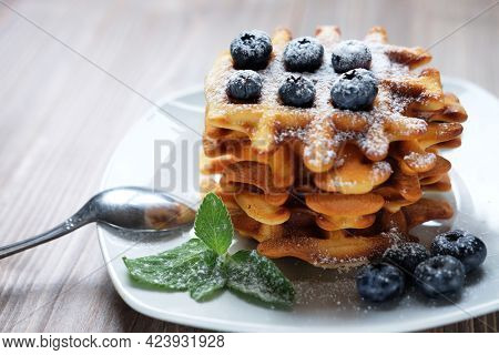 Homemade Belgian waffles served with fresh berries on white plate over wooden background, close up
