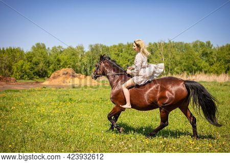 A Young Rider Woman Blonde With Long Hair In A Dress Riding Gallop On Brown Horse On A Field And For