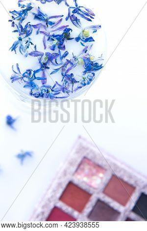 Eyeshadow Colorful Palette For Makeup And Crystal Glass With Milk And Blue Flower Petals On Light Ba