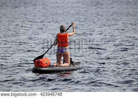 Woman In Swimsuit And Life Jacket Kneeling Down With Paddle On A Board In A Water. Standup Paddleboa