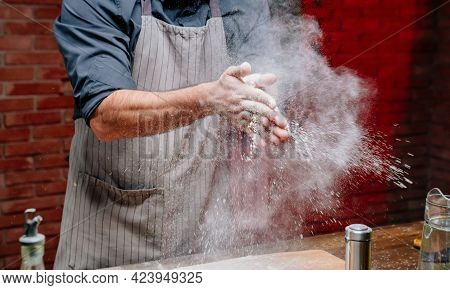 Man In An Apron Take Flour And Clap Their Hands. Scatter The Flour