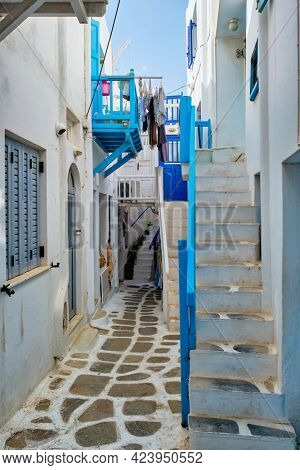Picturesque scenic narrow Greek streets with traditional whitewashed houses with blue doors windows of Mykonos town in famous tourist attraction Mykonos island, Greece
