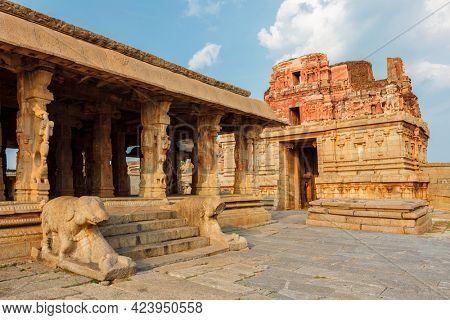 Pillared porch in Krishna Temple and gopura tower. Hampi, Karnataka, India