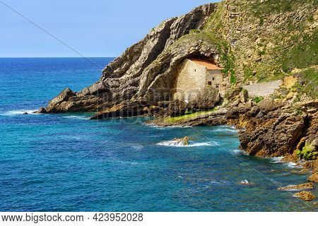 Stone House Tucked Between The Rocks On A Cliff From The Sea. Santander Spain.