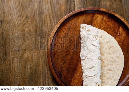 Rolled Flatbread Pita On A Round Wooden Cutting Board. Bakery. Flat Bread