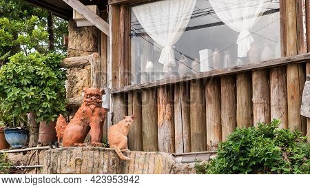 A Ginger Cat Sits Next To A Ceramic Lion-dog Shi-sa Figure Outside A Traditional Okinawan Dwelling.