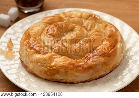 Single traditional Turkish borek stuffed with cheese on a plate
