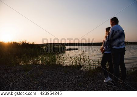 Pregnant Woman And Her Husband Relaxing By The Lake In The Sunset.
