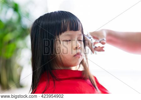 Cute Asian Girl Sitting And Eyes Closed. The Barber's Hands Skillfully Cut Front Hair Of Child. Kid