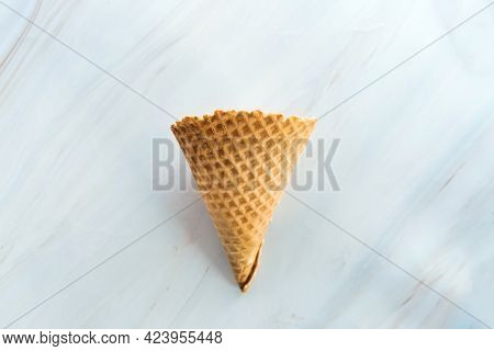 Empty Ice Cream Waffle Cone On Marble Background. Blank Wheat Wafer Cone For An Ice-cream
