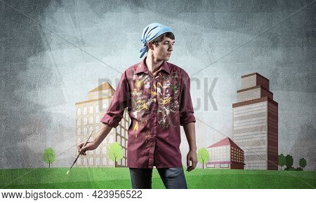 Young Male Artist Holding Paintbrush. Painter In Shirt And Bandana Standing On Background Colorful P