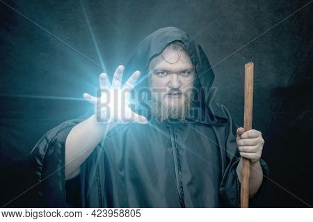From The Hand Of A Black-hooded Monk With A Staff, There Is A Glow On A Dark Background, A Gloomy Ex